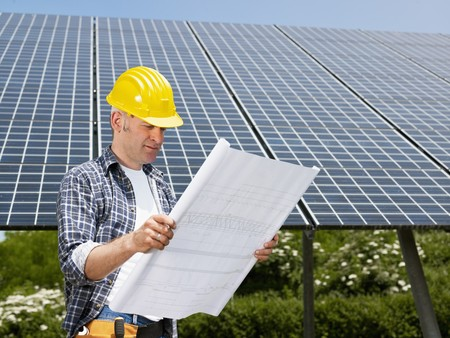 environmental issues: Portrait of mid adult italian male electrician reading blueprints in solar power station and smiling. Horizontal shape, side view. Copy space Stock Photo