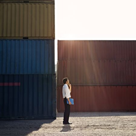 near side: Mid adult businessman standing near cargo container with hand on chin and looking up. Square shape, full length, side view, copy space