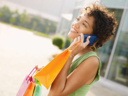 young woman talking on mobile phone out of shopping center. Horizontal shape, waist up, copy space photo