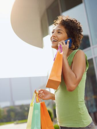 young woman talking on mobile phone out of shopping center. Vertical shape, waist up, copy space photo
