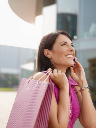 mid adult italian woman talking on mobile phone out of shopping center. Vertical shape, head and shoulders, copy space photo