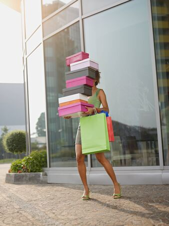 carrying girl: hispanic woman balancing stack of shoe boxes out of shopping center. Vertical shape, full length, copy space Stock Photo