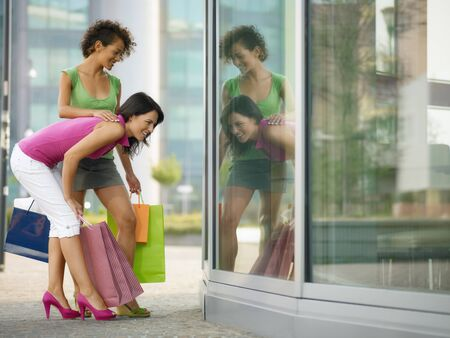 leisure centre: mid adult italian woman and hispanic woman looking at shop window with shopping bags. Horizontal shape, full length, copy space Stock Photo