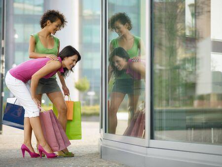 굽힘: mid adult italian woman and hispanic woman looking at shop window with shopping bags. Horizontal shape, full length, copy space 스톡 사진