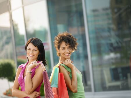 waist up: mid adult italian woman and hispanic woman carrying shopping bags out of shopping center. Horizontal shape, waist up, copy space
