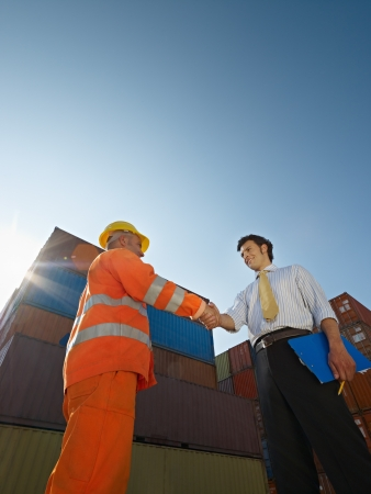 Mid adult businessman holding clipboard and shaking hands to manual worker near cargo containers. Vertical shape, low angle view. Copy space Stock Photo
