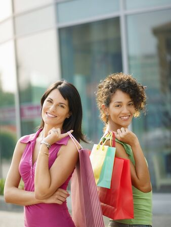 mid adult italian woman and hispanic woman carrying shopping bags out of shopping center. Vertical shape, waist up, copy space photo