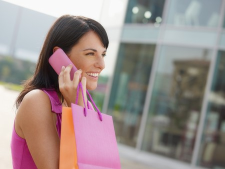 mid adult italian woman talking on mobile phone out of shopping center. Horizontal shape, head and shoulders, copy space photo