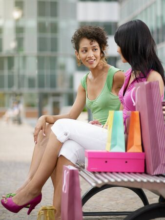 two women relaxing on bench after shopping. Vertical shape, full length, copy space photo