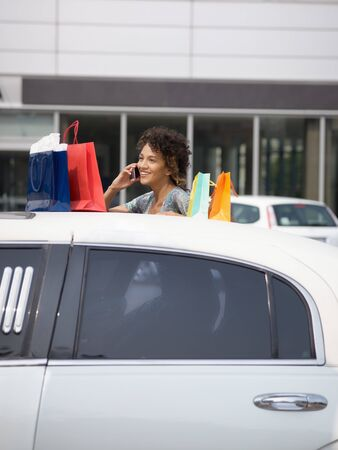 woman getting out of limousine with shopping bags. Vertical shape, copy space photo