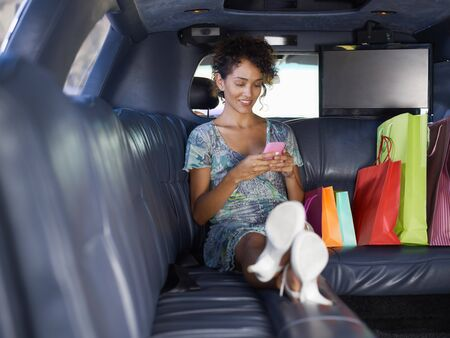 woman sitting in limousine with shopping bags and typing on mobile phone. Horizontal shape, full length, copy space photo
