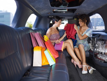 look inside: woman in limousine showing new dress to her friend. Horizontal shape, full length, copy space