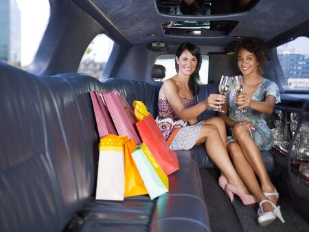 limo: women in limousine toasting with champagne. Horizontal shape, full length, copy space