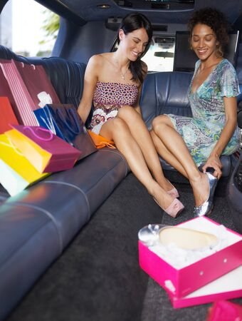 women in limousine trying on new shoes. Vertical shape, full length, copy space photo