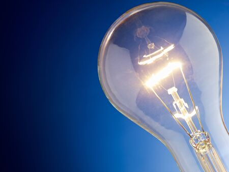 tungsten lightbulb on blue background. Horizontal shape, copy space photo