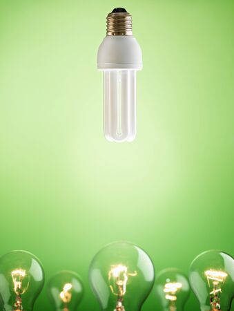 fluorescent lightbulb over large group of tungsten lights on green background. Vertical shape, copy space photo