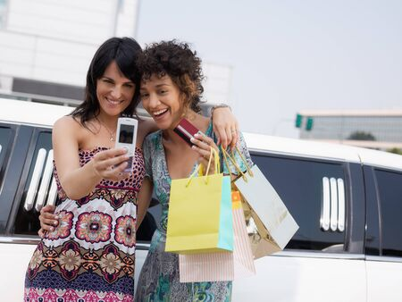 two women standing by limousine and taking picture on mobile phone. Horizontal shape, waist up, copy space Stock Photo - 7664820