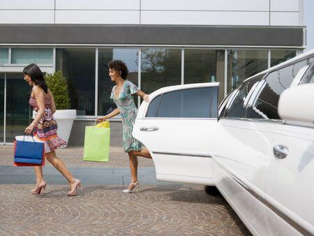 mujeres corriendo: dos mujeres que se ejecuta fuera de la limusina con bolsas de compra. Forma horizontal, de longitud completa