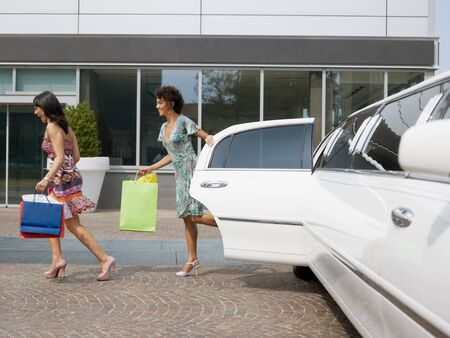 limo: two women running out of limousine with shopping bags. Horizontal shape, full length Stock Photo