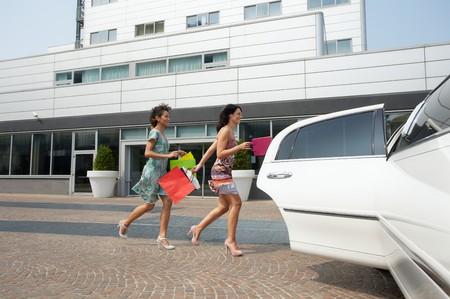 mujeres corriendo: dos mujeres que se ejecuta en limusina con bolsas de compra. Forma horizontal, de longitud completa
