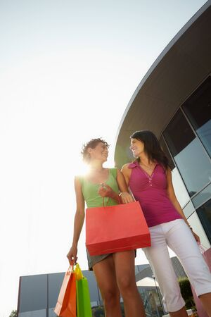 leisure centre: mid adult italian woman and hispanic woman carrying shopping bags out of shopping center at sunset. Vertical shape, low angle view, copy space