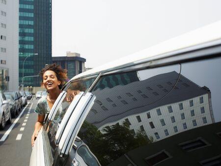 adentro y afuera: mujer hispana en limusina con cabeza fuera de la ventana del coche. Forma horizontal, el espacio de copia