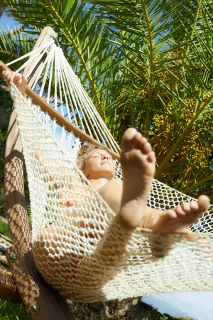 feet crossed: woman relaxing on hammock with eyes closed. Low angle view, Vertical shape Stock Photo