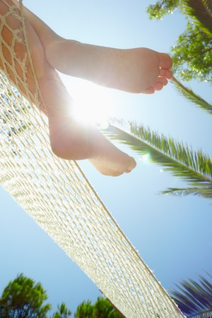 rilassato: cropped view of woman relaxing on hammock. Low angle view, Vertical shape