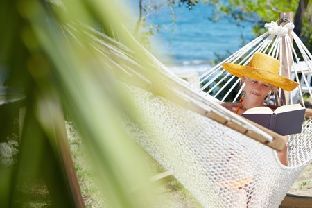 mid adult woman with orange hat reading book on hammock. Front view, Horizontal shape, copy space photo