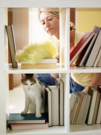 dusting: mid adult woman dusting bookshelves. Vertical shape, three quarter length