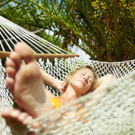 feet crossed: woman relaxing on hammock with eyes closed. Front view, Square  shape Stock Photo