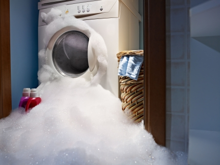 inconvenience: soap coming out from broken washing machine. Stock Photo