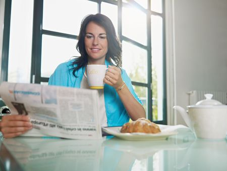 mid adult woman drinking coffee and reading news. Horizontal shape, copy space photo