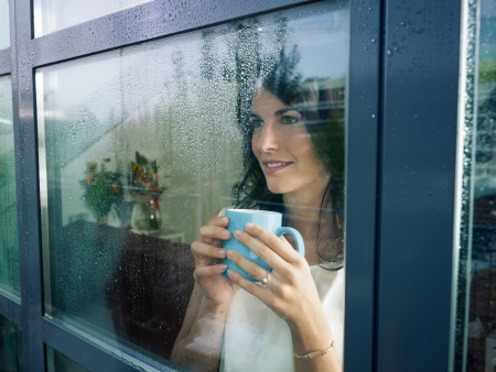 windows: mid adult woman drinking coffee and looking out of the window on rainy day. Horizontal shape