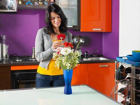 arrange: mid adult woman putting gerbera in blue pot. Horizontal shape, three quarter length Stock Photo