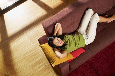 ハイアングルビュー: 彼女の新しい家のソファーに横たわっている女性。コピー スペース完全な長さ、ハイアングル水平] 図形