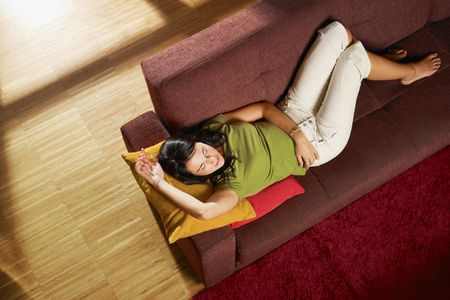 Woman lying down on sofa in her new house. Horizontal shape, high angle view, full length, copy space Stock Photo - 8006006