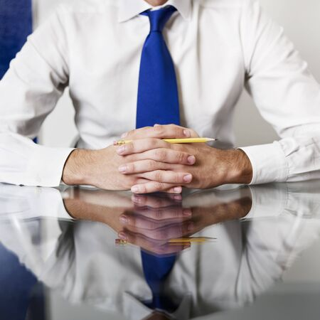 sitting at table: cropped view of businessman with hands clasped. Square shape, front view Stock Photo