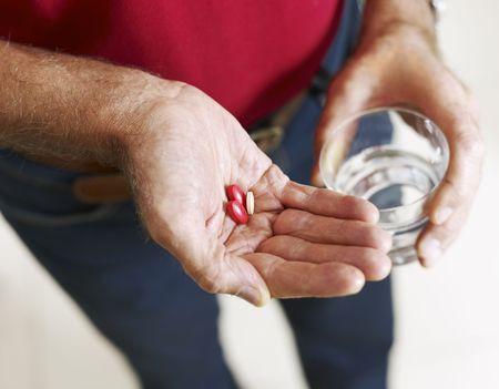pills in hand: Cerca del hombre senior tomando medicamentos. Forma horizontal, el �ngulo de alta vista, el enfoque selectivo  Foto de archivo