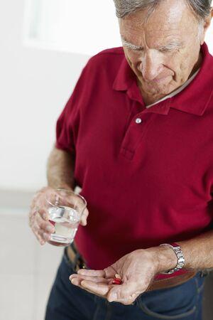 Senior man holding pills. Vertical shape, side view, waist up photo