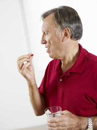 Senior man taking medicine. Vertical shape, Side view, Copy space photo