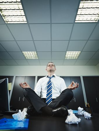 messy desk: stressed businessman sitting on desk in lotus position. Vertical shape, full length, Copy space