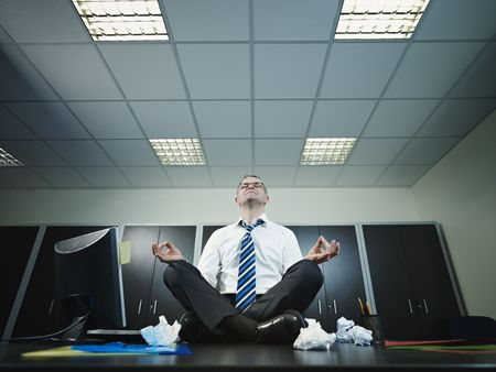 patience: Mature businessman sitting on desk in lotus position. Horizontal shape, full length, Copy space