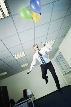 mature business man holding colored balloons and flying in office. Vertical shape, full length, Copy space Stock Photo - 8006020