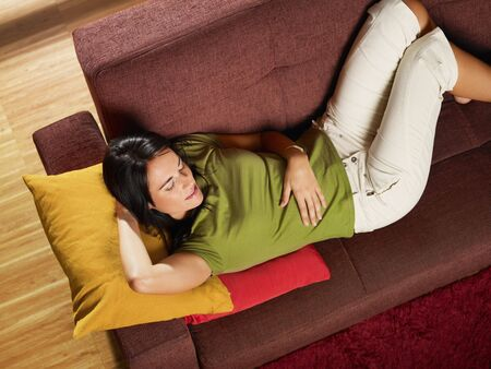 Woman lying down on sofa. Horizontal shape, high angle view, three quarter length, copy space photo