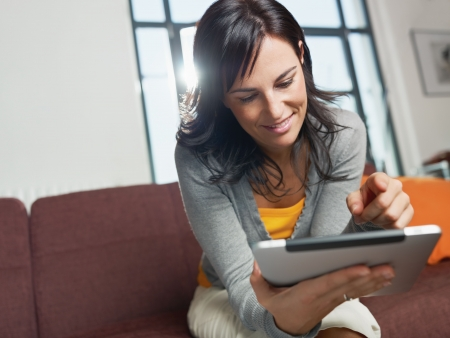 a person: mid adult woman sitting on sofa with tablet pc. Horizontal shape, front view, copy space