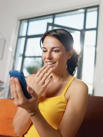 mid adult woman sitting on sofa, getting good news on mobile phone. Vertical shape, side view, waist up photo
