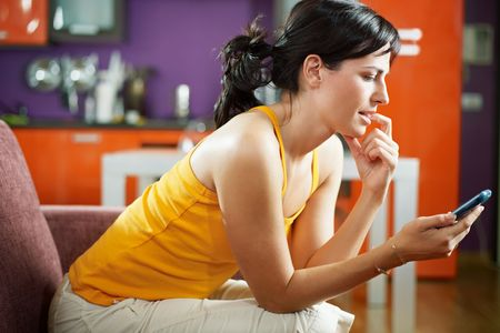 mid adult woman on sofa staring at her mobile phone and biting nails. Horizontal shape, waist up, copy space photo