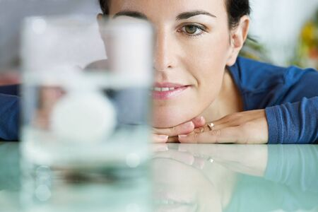cropped view of mid adult woman leaning on table and looking at effervescent tablet dissolving in water. Horizontal shape, front view, copy space
