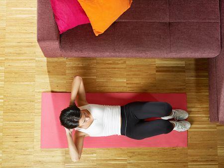 ハイアングルビュー: ミッド アダルト女性トレーニング腹筋自宅と使用。横型形状、完全な長さ、ハイアングル コピー スペース